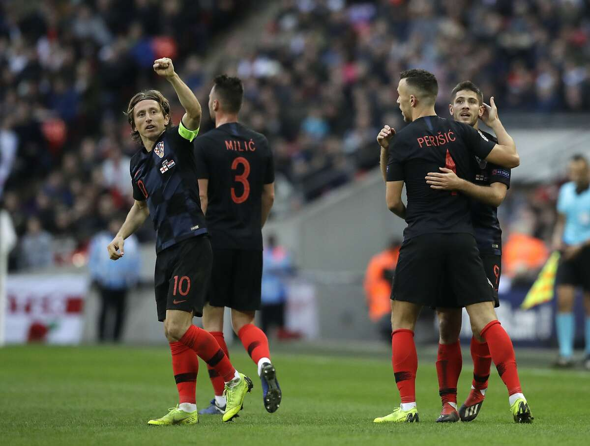 Croatia's Luka Modric gestures as Croatia's players celebrate their side's first goal, scored by Croatia's Andrej Kramaric, right, during the UEFA Nations League soccer match between England and Croatia at Wembley stadium in London, Sunday, Nov. 18, 2018. (AP Photo/Matt Dunham)