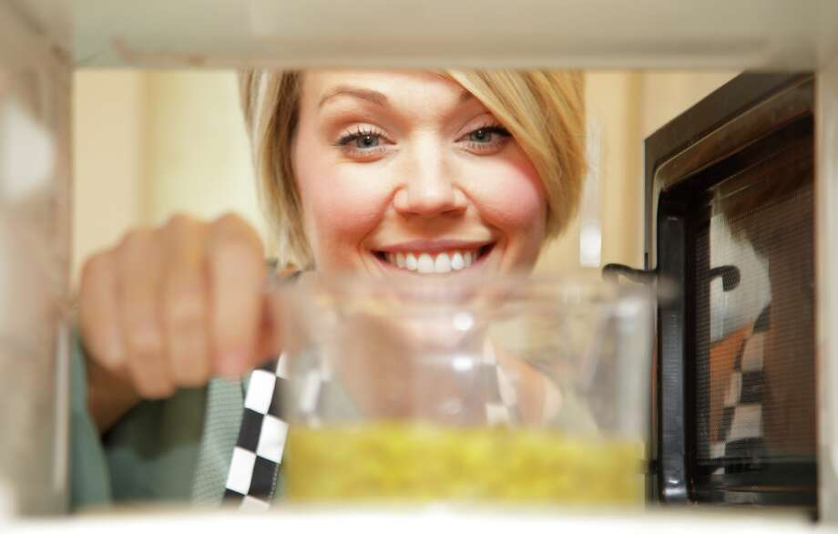 She's smiling now, but she won't be if she gets sick from reheated rice that's gone bad, say some so-called cooking experts. Does reheating certain foods in a microwave oven really pose a hazard to your health? Or is it just overly cautious blather? We take a look. Photo: ALISTAIR SHANKIE/Getty Images / SHANK ALI