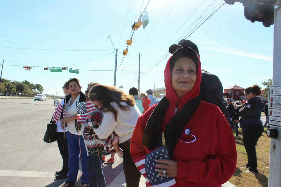 """Debra Alanis, a 55-year old retired secretary, stood on the corner of Dixie Farm Road and Texas 3 to catch a glimpse of the motorcade carrying the casket of former President George H.W. Bush to Ellington Airport. """"I just feel a spiritual connection and wanted to pay my respects to a wonderful man,"""" says Alanis, who lives near the airport."""