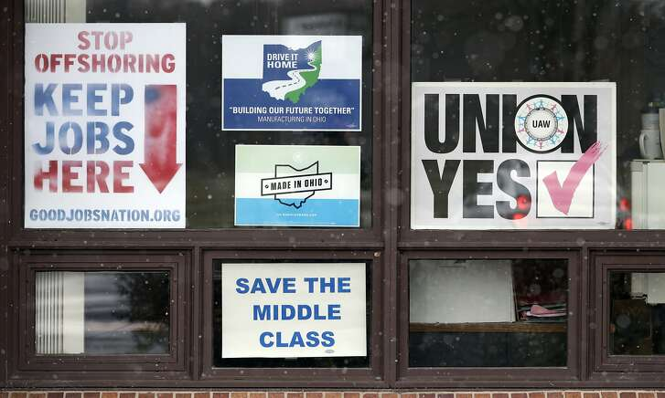 In this Nov. 27, 2018 photo, signs hang from windows at the UAW Local 1112 union hall, in Lordstown, Ohio. It was working-class voters who bucked the area's history as a Democratic stronghold and backed Donald Trump in 2016, helping him win the White House with promises to put American workers first and bring back disappearing manufacturing and steel jobs. Whether they stick with him after this week's GM news and other signs that the economy could be cooling will determine Trump's political future. (AP Photo/Tony Dejak)