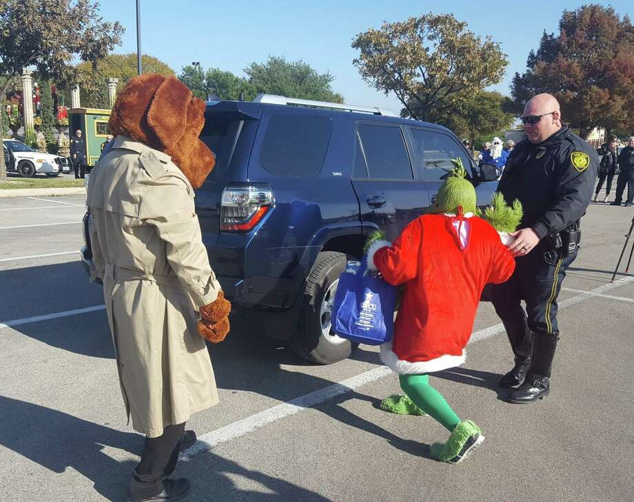 "Selma Police Officer Matt Faseler moves in to arrest The Grinch, who McGruff The Crime Dog reported as being a suspicious person during an ""Operation Grinch"" kickoff event at The Forum at Olympia Parkway recently. Photo: Jeff B. Flinn / Staff Photographer"
