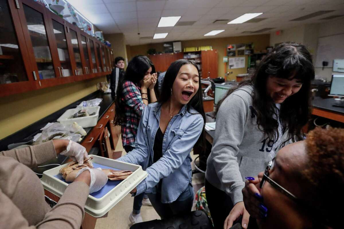 Aliya Phrakonkham, 15, center, reacts as her biology teacher, Ronshon Jeffery, gives her a squid for a dissection assignment, at Victory Early College High School Wednesday, May 9, 2018, in Houston. ( Jon Shapley / Houston Chronicle )