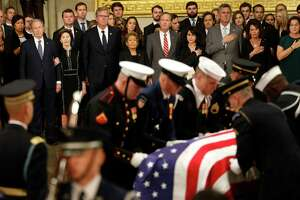 Pallbearers bring in the casket of President George H.W. Bush as members of the family stand and watch during the State Funeral of for him at the United States Capitol Rotunda, Monday, Dec. 3, 2018, in Washington. Bush will lie in state in the Rotunda until Wednesday morning.