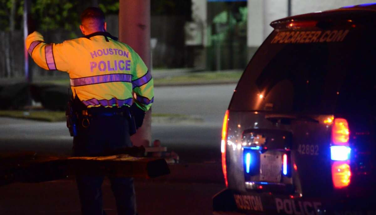 Houston police officers investigate a deadly crash involving a dump truck along the South Sam Houston Parkway feeder road at Telephone Road on Monday, Dec. 3, 2018.