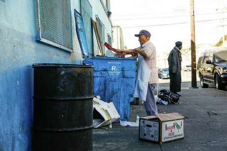 A man breaks down recycling as a homeless man named Eric (right) hands out outside Mother Brown's Dining Room in the Bayview neighborhood in San Francisco, California, on Wednesday, Oct. 31, 2018. Photo: Gabrielle Lurie / The Chronicle / ONLINE_YES