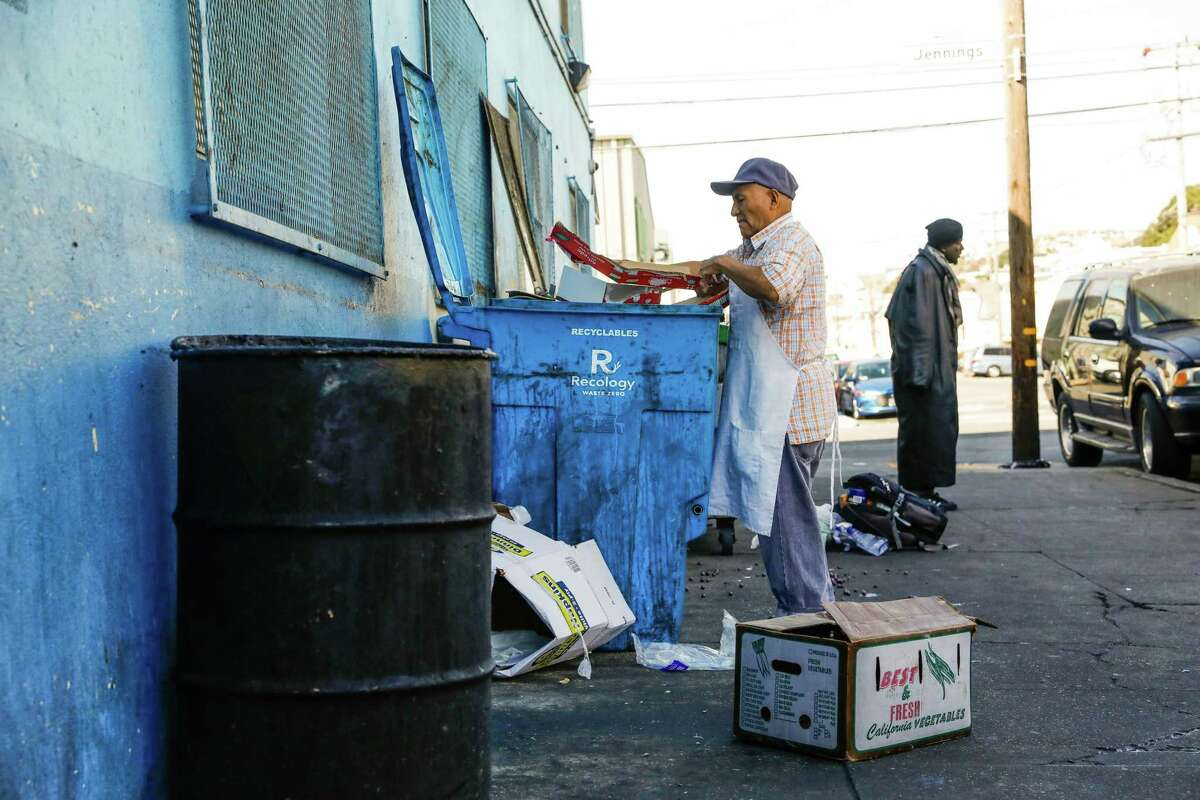 A man breaks down recycling as a homeless man named Eric (right) hands out outside Mother Brown's Dining Room in the Bayview neighborhood in San Francisco, California, on Wednesday, Oct. 31, 2018.