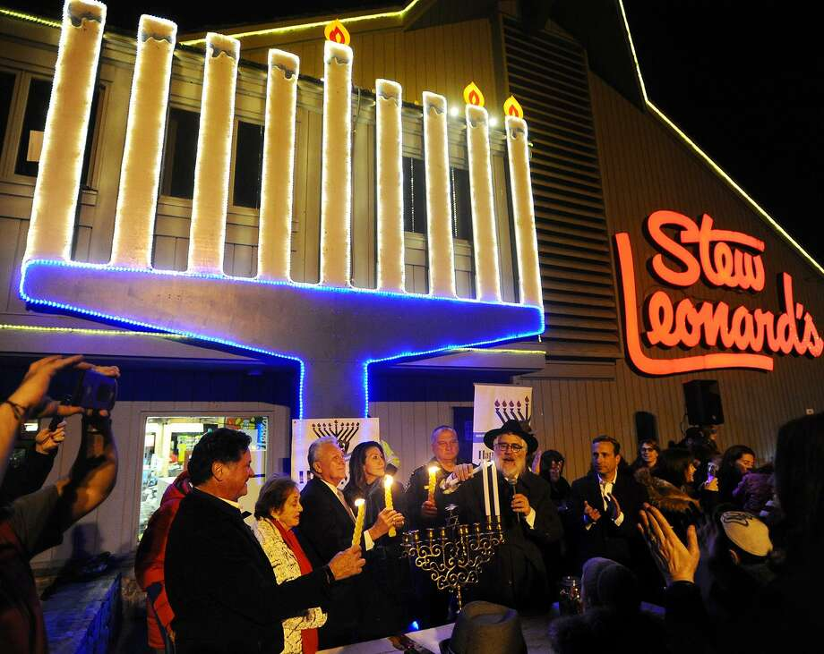 Rabbi Yehoshua Hecht of Beth Israel of Westport/ Norwalk lights the menorah on the second night of Hanukkah outside Stew Leonard's in Norwalk, Conn. on Monday, December 3, 2018. Dignitaries from left are Stew Leonard, Jr., Marianne Leonard, Norwalk Mayor Harry Rilling, Lucia Rilling, Police Chief Thomas Kulhawik, Hecht, and State Senator Bob Duff. Photo: Brian A. Pounds / Hearst Connecticut Media / Connecticut Post