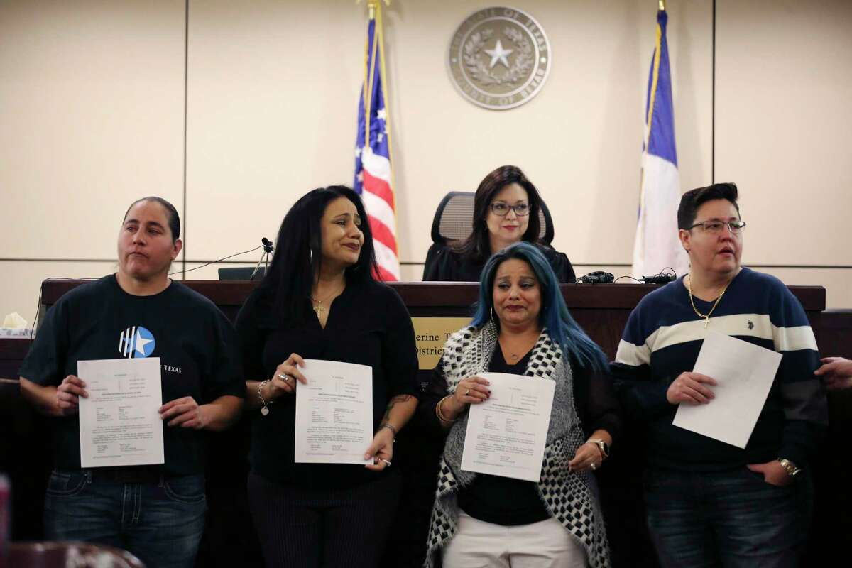 """Holding back emotions, the """"San Antonio Four"""" - from left, Anna Vasquez, Cassandra Rivera, Elizabeth Ramirez and Kristie Mayhugh - hold their orders granting the expunction of their criminal records signed by Bexar County 175th Criminal District Court Judge Catherine Torres-Stahl, shown in the back, on Dec. 3, 2018."""