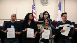 "Holding back emotions, the ""San Antonio Four"" — from left, Anna Vasquez, Cassandra Rivera, Elizabeth Ramirez and Kristie Mayhugh — hold their orders granting the expunction of their criminal records signed by Bexar County 175th Criminal District Court Judge Catherine Torres-Stahl, shown in the back, on Dec. 3, 2018."