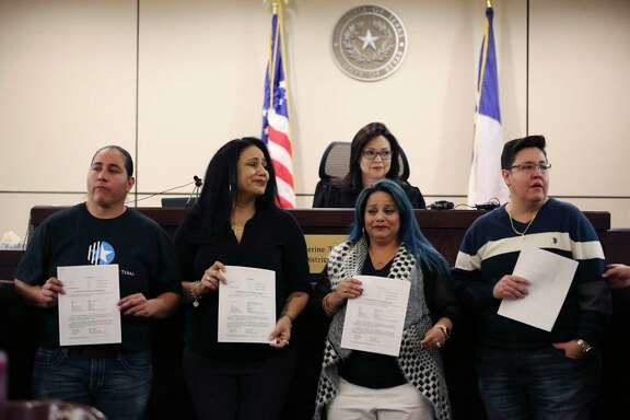 """Holding back emotions, the """"San Antonio Four"""" — from left, Anna Vasquez, Cassandra Rivera, Elizabeth Ramirez and Kristie Mayhugh — hold their orders granting the expunction of their criminal records signed by Bexar County 175th Criminal District Court Judge Catherine Torres-Stahl, shown in the back, on Dec. 3, 2018."""