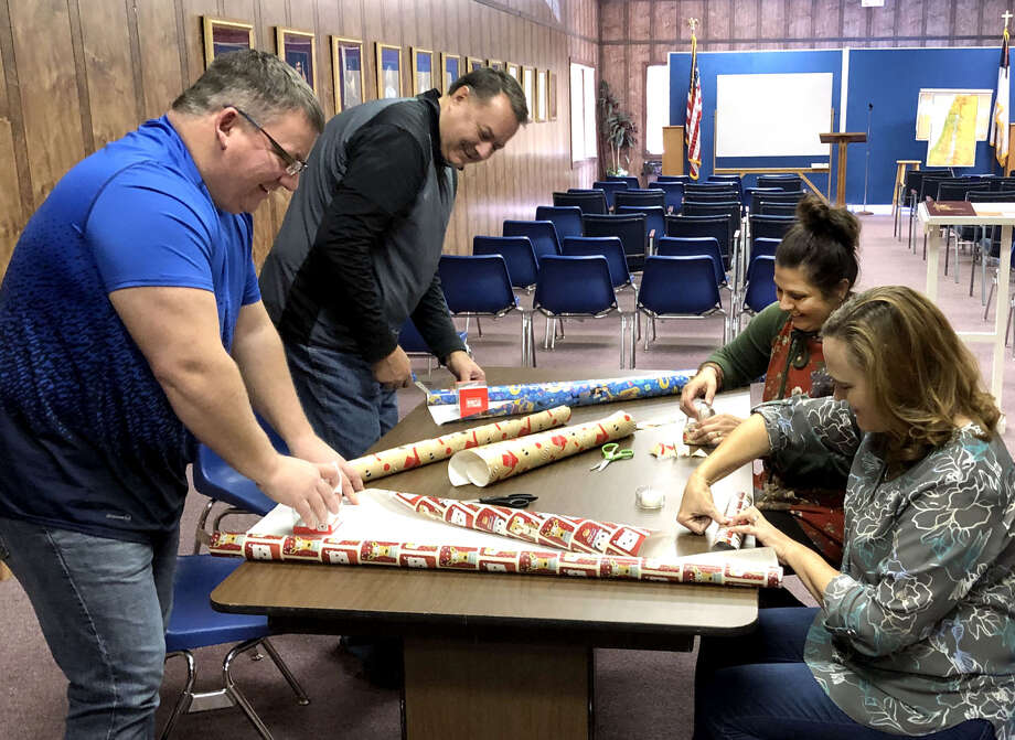 Hope Hastey (top right), founder of RADAR Foundations, Inc. and organizer of Thursday's Sensory Santa celebration, is joined by Lori Brown, Tim Penney and Greg Northcutt, staff members of Plainview's First Baptist Church, as they wrap presents in preparation for the event. RADAR Foundations has partnered with First Baptist Church to provide the celebration for special needs children. It will be in conjunction with the annual Christmas Parade and will be held from 5-7 p.m. at The Pastor's Class building on the southwest corner of Seventh Street and Broadway. Photo: Richard Porter/Courtesy Photo