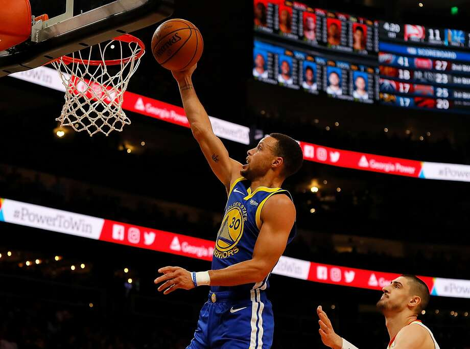 Stephen Curry of the Golden State Warriors lays in a basket against Alex Len #25 of the Atlanta Hawks at State Farm Arena on December 3, 2018 in Atlanta, Georgia. Photo: Kevin C. Cox / Getty Images