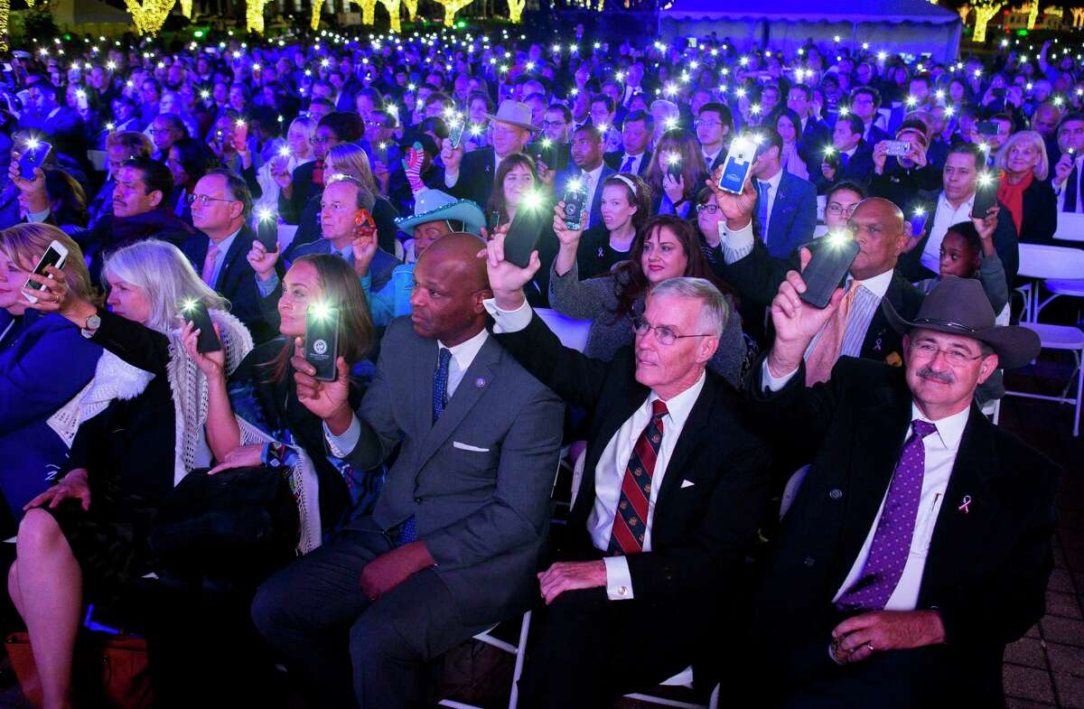 People hold up their phones during the singing of Hallelujah by Clay Walker during a tribute to President George H.W. Bush at City Hall in Houston, Monday, Dec. 3, 2018 in Houston.