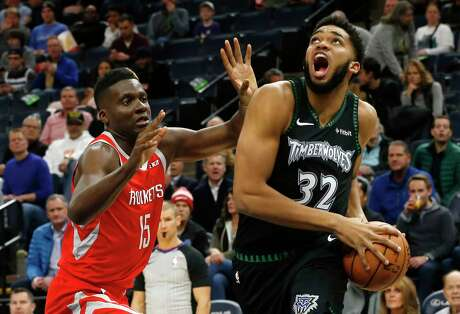 Minnesota Timberwolves' Karl-Anthony Towns, right, eyes the basket as Houston Rockets' Clint Capela of Switzerland defends in the first half of an NBA basketball game Monday, Dec. 3, 2018, in Minneapolis. (AP Photo/Jim Mone)