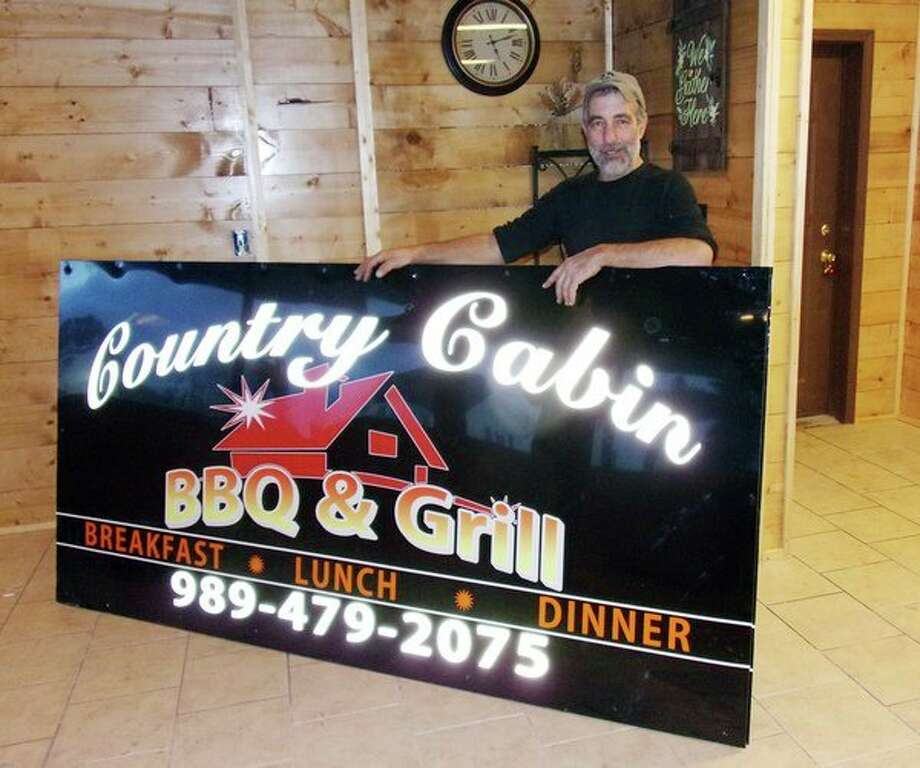 Country Cabin BBQ & Grill's co-owner, George Abbo, stands next to the restaurant's new sign before it was erected in front of the Harbor Beach eatery. It is scheduled to open Tuesday, Dec. 11. The sign was made by Complete Computer and Sign Shop of Bad Axe. (Rich Harp/For the Tribune)