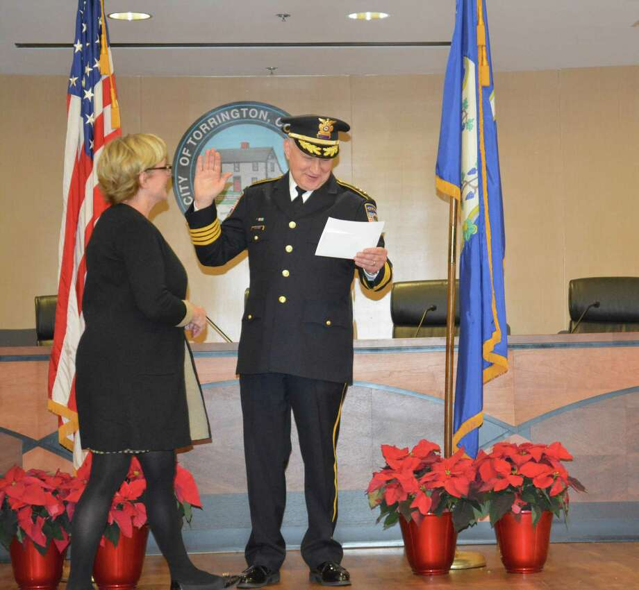 The oath of office for the swearing-in ceremony was a bit wordy, so Mayor Elinor Carbone handed the document to new Torrington Police Chief William Baldwin, so he could read it directly to the audience. Photo: Leslie Hutchison / Hearst Connecticut Media /