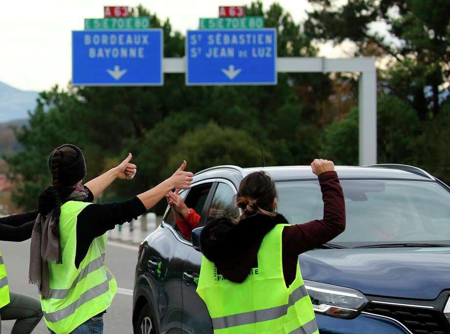 """Demonstrators open the toll gates on motorway near Biarritz, southwestern France, Monday, Dec. 3, 2018. French Prime Minister Edouard Philippe is holding crisis talks with representatives of major political parties in the wake of violent anti-government protests that have rocked Paris. The """"yellow vest"""" movement is bringing together people from across the political spectrum complaining about France's economic inequalities and waning spending power. (AP Photo/Bob Edme) Photo: Bob Edme / Copyright 2018 The Associated Press. All rights reserved."""