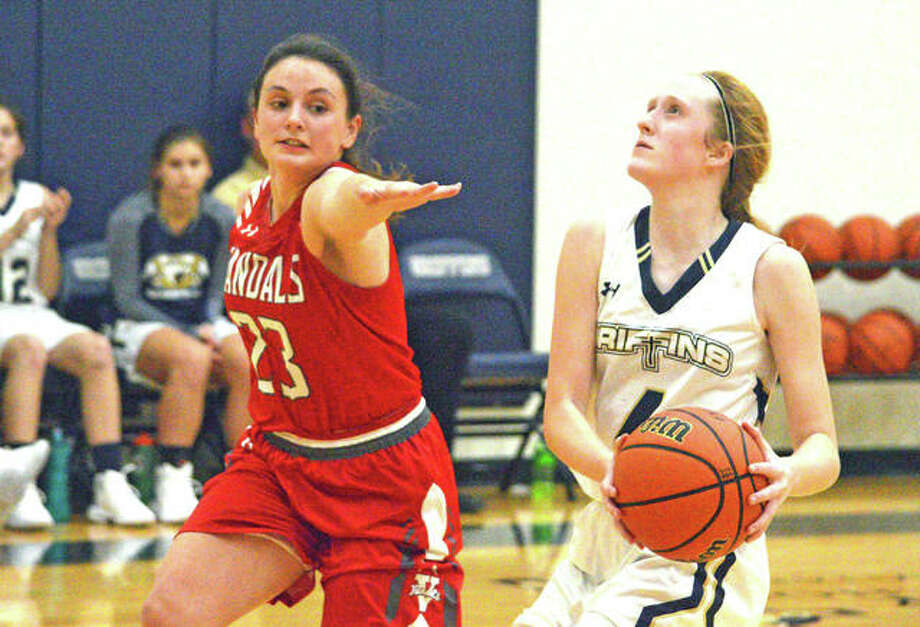 Father McGivney sophomore Anna McKee, right, drives to the basket during Monday's home game against Vandalia. Photo: Scott Marion/Intelligencer