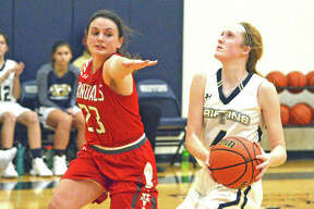 Father McGivney sophomore Anna McKee, right, drives to the basket during Monday's home game against Vandalia.