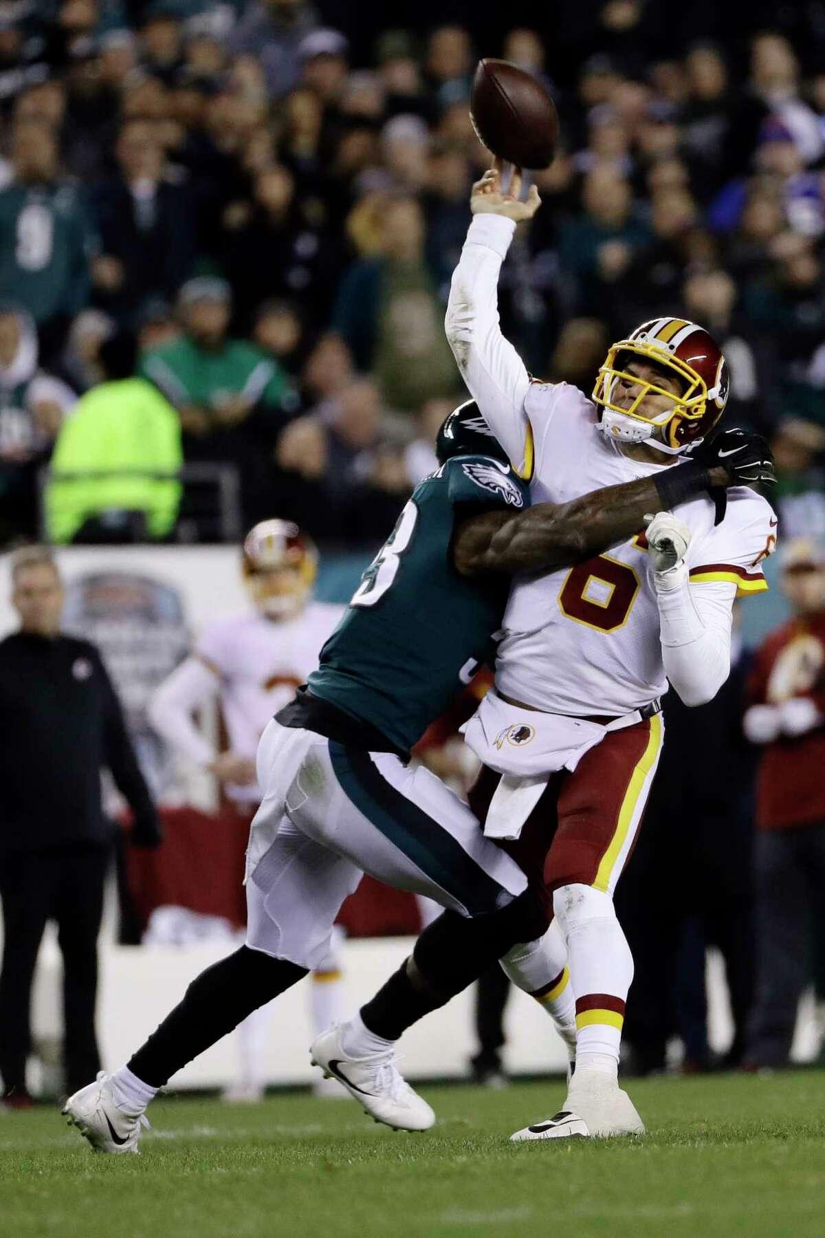 Washington Redskins' Mark Sanchez (6) is hit by Philadelphia Eagles' Nigel Bradham (53) during the first half of an NFL football game, Monday, Dec. 3, 2018, in Philadelphia.