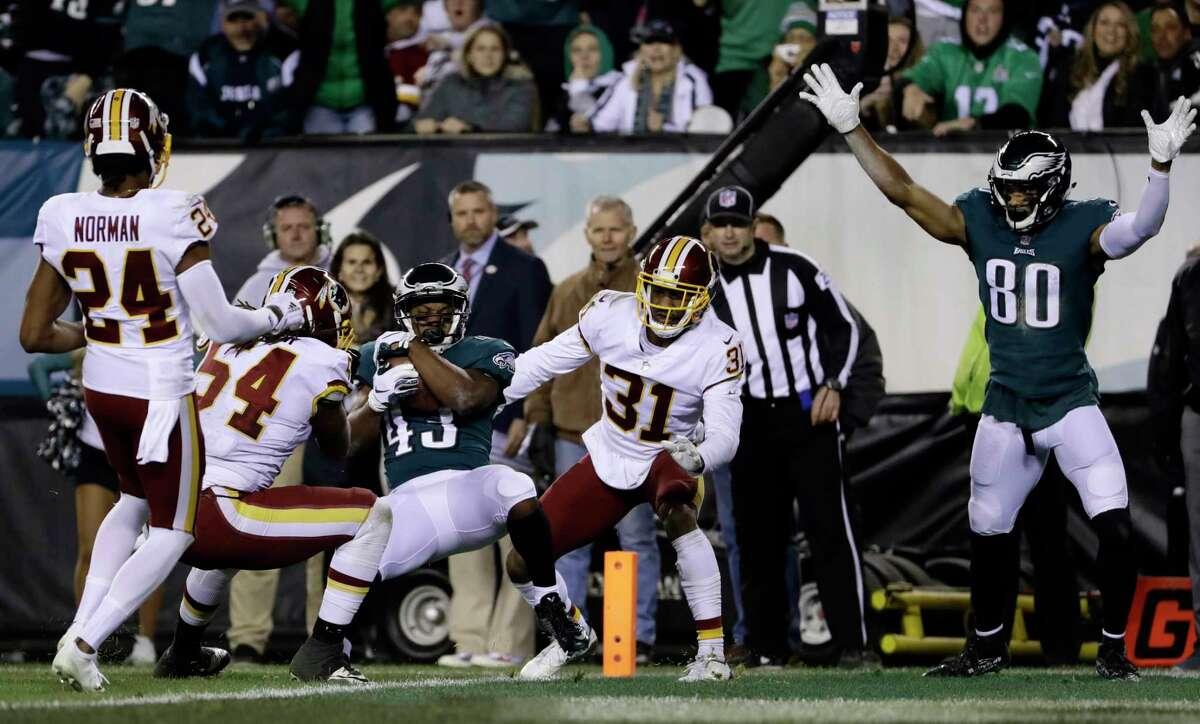 Philadelphia Eagles' Darren Sproles (43) scores a touchdown against Washington Redskins' Fabian Moreau (31), Mason Foster (54) and Josh Norman (24) during the first half of an NFL football game, Monday, Dec. 3, 2018, in Philadelphia.
