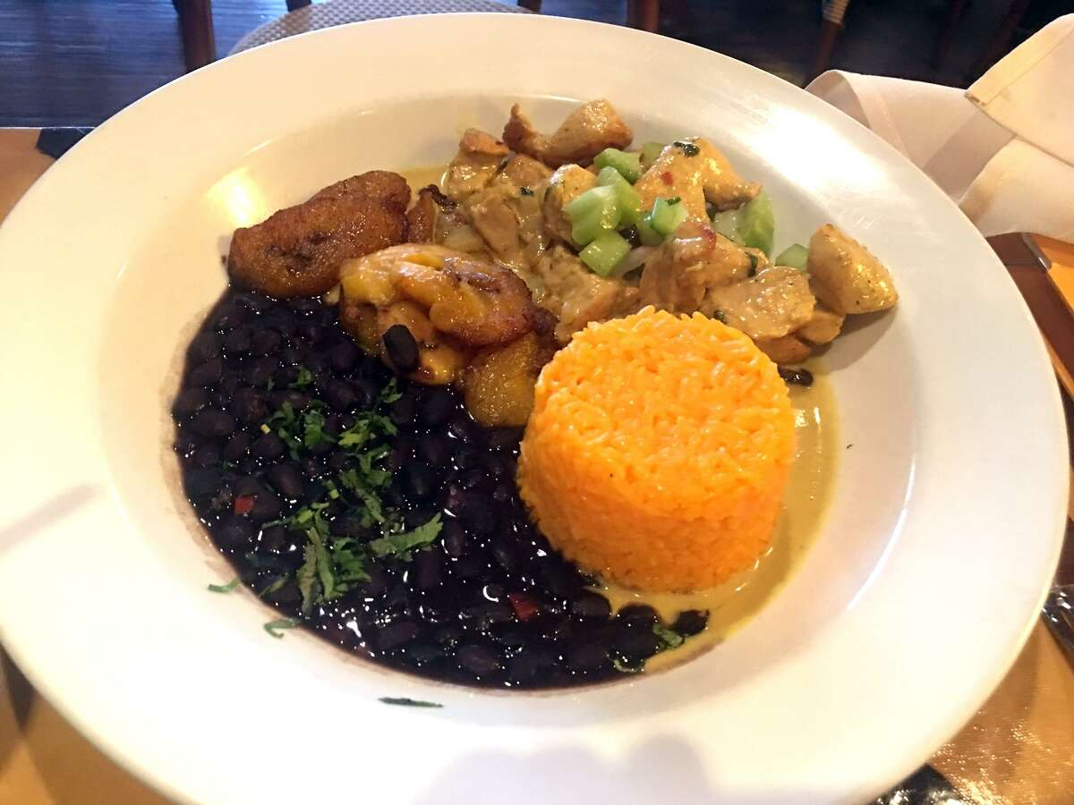 Brasitas' curried version of arroz con pollo has shreds of chicken are sautéed in a coconut curry sauce, to which has been added celery hearts, Chilean raisins, yellow jasmine rice, sweet fried plantains and fabulous black beans.