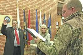 Cromwell Fire District President LeRoy D. Brow, left, swears in new commissioner Charles Epstein following voting Monday, as Epstein's wife Diana looks on.