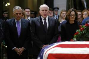 Former CIA directors George Tenet, left, and John Brennan pause alongside current director Gina Haspel in front of the flag-draped casket of former President George H.W. Bush as he lies in state in the Capitol Rotunda in Washington, Tuesday, Dec. 4, 2018. (AP Photo/Patrick Semansky)