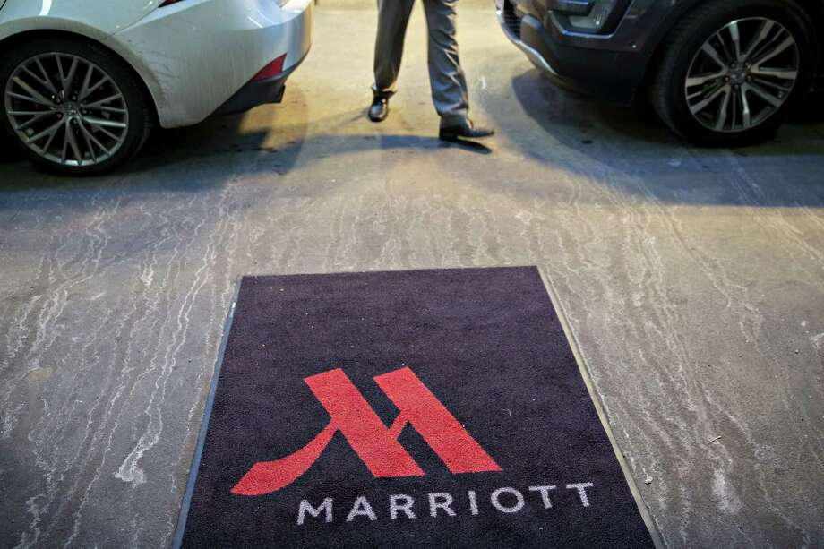 A logo is displayed on a rug outside a Marriott International Inc. hotel in Chicago on Nov. 30, 2018.   What crimes are American's worried about? >>>>  Photo: Bloomberg Photo By Daniel Acker. / © 2018 Bloomberg Finance LP