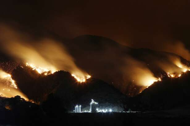 California wildfires Smoke from the Holy Fire burning in Cleveland National Forest is blurred in a long exposure above an industrial storage facility on August 10, 2018 in Corona, California. The fire continues to grow amidst a heat wave and has now burned over 18,000 acres while remaining just five percent contained.