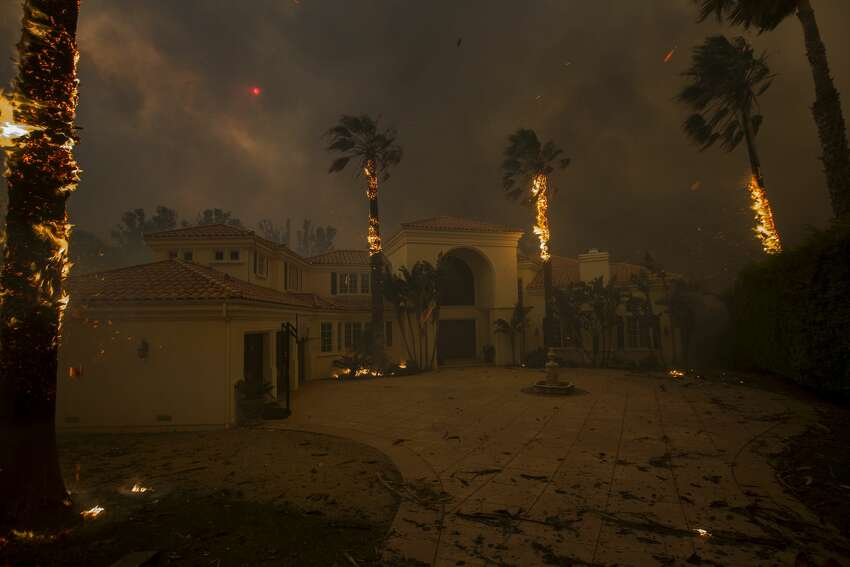 >>>See 2018's world news in photos. California wildfires Embers falls from burning palms and the sun is obscured by smoke as flames close in on a house at the Woolsey Fire on November 9, 2018 in Malibu, California. About 75,000 homes have been evacuated in Los Angeles and Ventura counties due to two fires in the region.