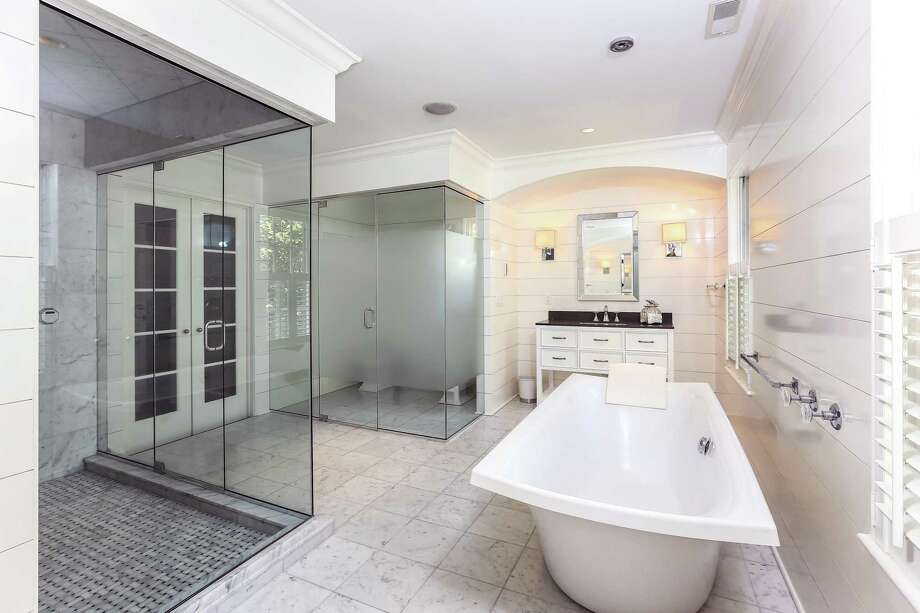 The marble master bath has a large steam shower, heated floors, soaking tub, and a frosted glass water closet. Photo: PlanOmatic / © 2017 PlanOmatic