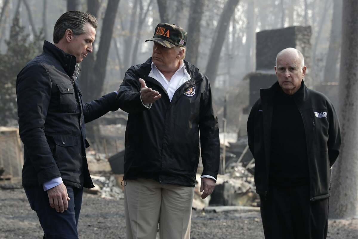 President Donald Trump talks with Gov.-elect Gavin Newsom, left, and as California Gov. Jerry Brown listens during a visit to a neighborhood impacted by the wildfires, Saturday, Nov. 17, 2018, in Paradise, Calif. (AP Photo/Evan Vucci)