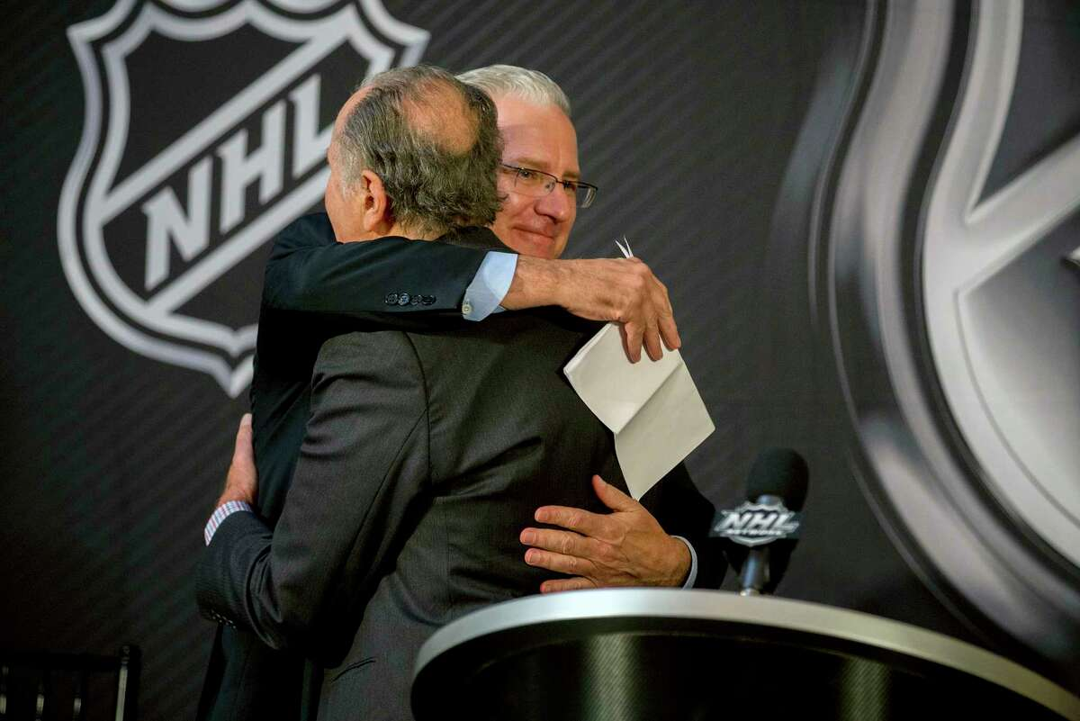 Seattle Hockey Partners president and CEO Tod Leiweke, right, is hugged by National Hockey League Commissioner Gary Bettman after the announcement by National Hockey League Board of Governors to name Seattle as the home of the league's 32nd franchise, Tuesday, Dec. 4, 2018, in Sea Island, Ga.