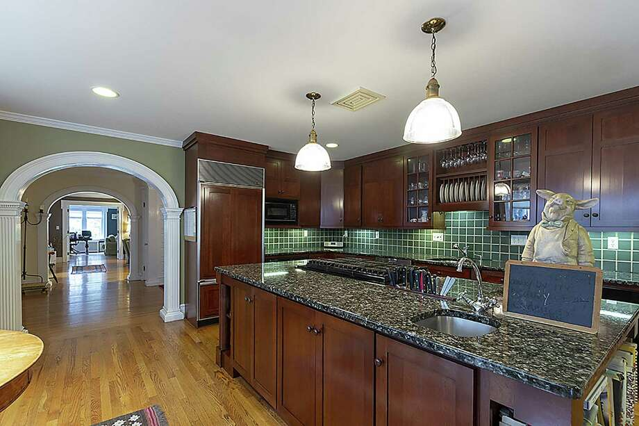 The remodeled kitchen at 29 Hartford Turnpike in Hamden features a wide archway, indicative of architect Alice Washburn's design. It includes a center island, granite counters and top-of-the-line appliances. Photo: Press|Cuozzo Realtors / ONLINE_CHECK