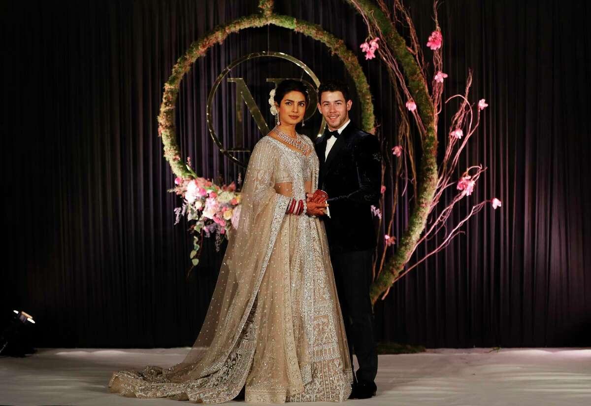 Bollywood actress Priyanka Chopra and musician Nick Jonas stand for photographs at their wedding reception in New Delhi, India, Tuesday, Dec. 4, 2018. (AP Photo/Altaf Qadri)