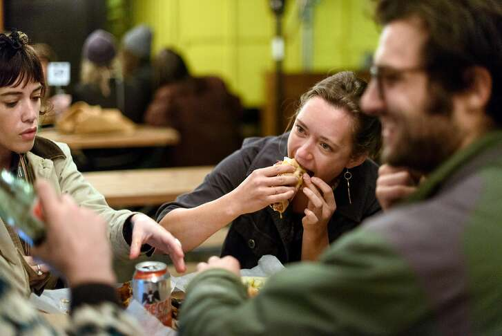 Cayley Eller bites into a taco as she and Syd Skorich, left, and Arlo Perlstein eat at Tacos Oscar's new permanent home in Oakland, California, on Friday, November 30, 2018.