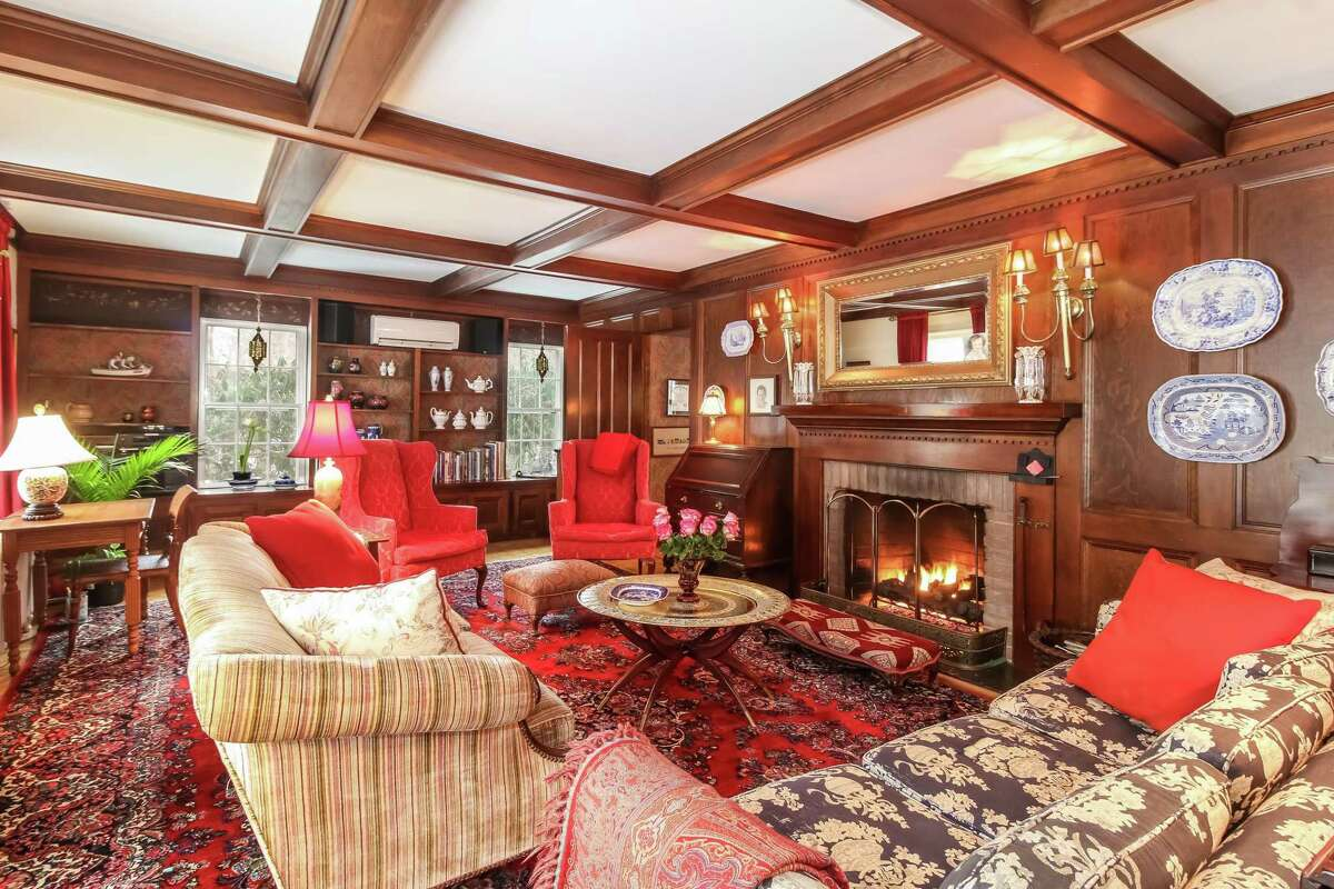 The family room at 82 Obtuse Road South in Brookfield has a second wood-burning fireplace with a wood mantel, built-in bookshelves with cabinetry and windows that overlook the property. Built in 1783, the antique farmhouse was a stop on the Underground Railroad.