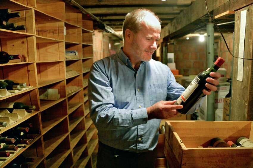 New owner Joe Maloney examines old wines in the cellar of The Wine Shop Tuesday Dec. 4, 2018 in Albany, NY. The Wine Shop is celebrating its 85th anniversary, opening the day Prohibition ended on Dec. 5, 1933. (John Carl D'Annibale/Times Union)