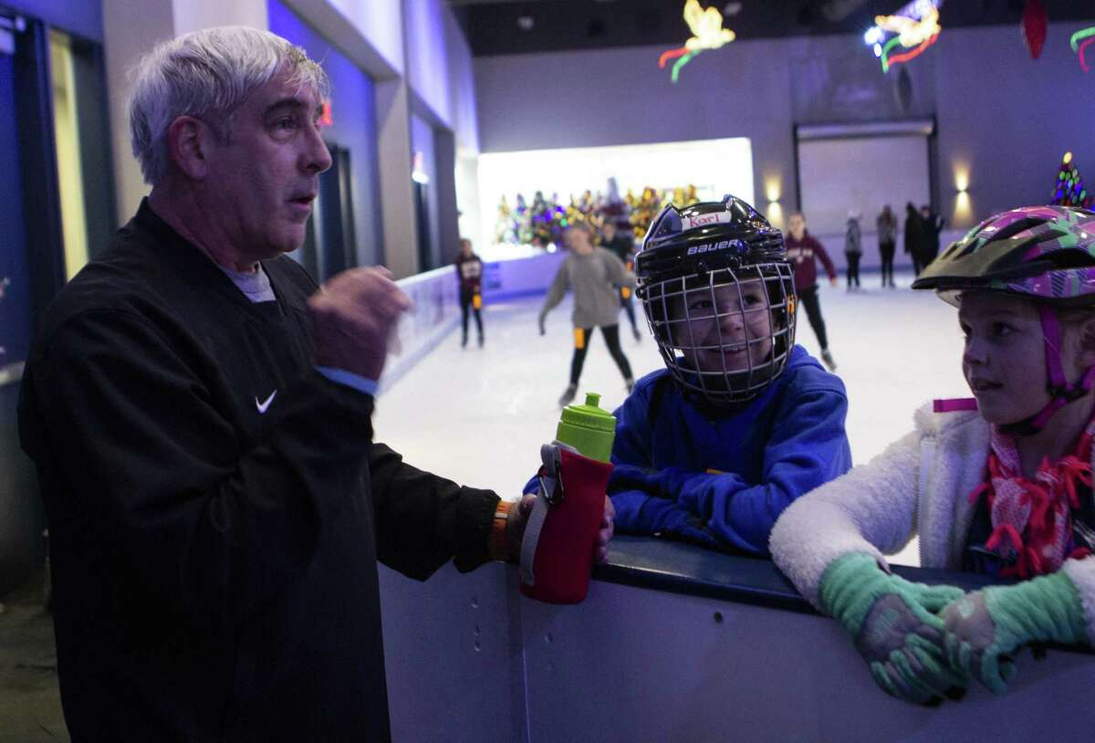 Kingwood resident David Miniter explains the importance of being an experienced ice skater when playing the goalie position in hockey to Karl Frankovitch, 9, and Mary Frankovitch, 9, at The Ice Rink at The Woodlands Town Center on opening day Saturday, Nov. 17, 2018 in The Woodlands.