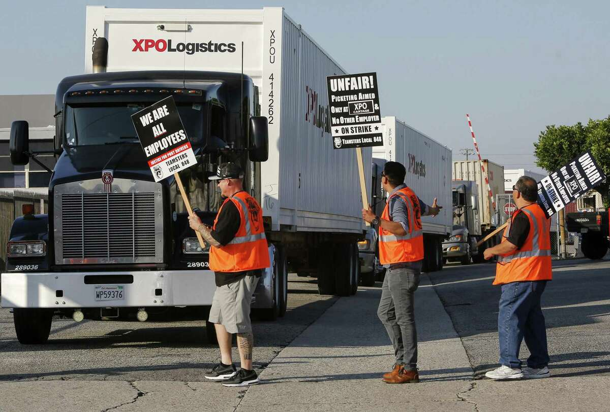 Port truck drivers picket at XPO Logistics in Commerce in 2017. On Saturday, Gov. Jerry Brown signed a bill that holds retailers jointly liable for labor law violations at California ports.