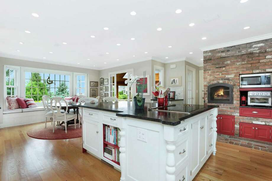 The open concept kitchen at 48 York St. in Stratford features custom cabinetry, a Wolf induction cooktop, a SubZero refrigerator, leather-finish granite island and built-in buffet and a stunning brick wall with fireplace and built-in appliances and cabinets. Photo: William Raveis Real Estate / ONLINE_CHECK