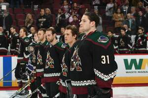GLENDALE, AZ - DECEMBER 01:  Adin Hill #31 of the Arizona Coyotes and teammates stand on the blue line during the playing of the national anthem against the St Louis Blues at Gila River Arena on December 1, 2018 in Glendale, Arizona.  (Photo by Norm Hall/NHLI via Getty Images)