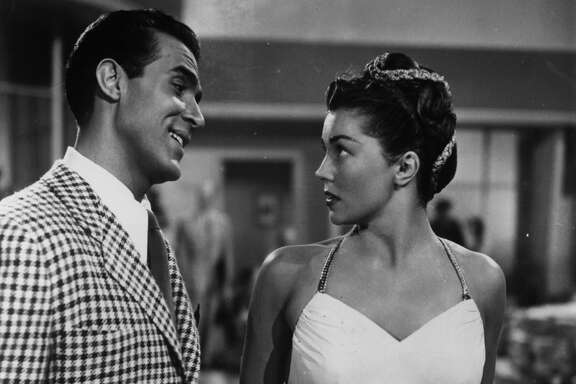 """Ricardo Montalban smiling at Esther Williams in a scene from the film """"Neptune's Daughter,"""" 1949. """"Baby It's Cold Outside"""" was first popularized in the movie."""