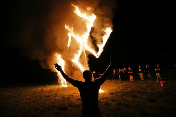 White Nationalists Rally Members of the National Socialist Movement, one of the largest neo-Nazi groups in the US, hold a swastika burning after a rally on April 21, 2018 in Draketown, Georgia. Community members had opposed the rally in Newnan and came out to embrace racial unity in the small Georgia town. Fearing a repeat of the violence that broke out after Charlottesville, hundreds of police officers were stationed in the town during the rally in an attempt to keep the anti racist protesters and neo-Nazi groups separated.