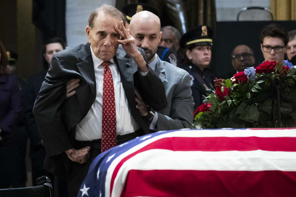 Former Senator Bob Dole stands up and salutes the casket of the late former President George H.W. Bush as he lies in state at the U.S. Capitol, December 4, 2018 in Washington, DC.