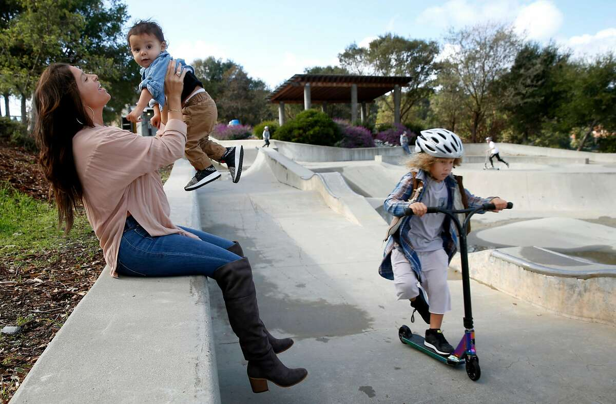 Kelli Peterson holds Che, 1, while her oldest son Kin, 5, whizzes past at a skatepark in San Rafael, Calif. on Saturday, Dec. 1, 2018.