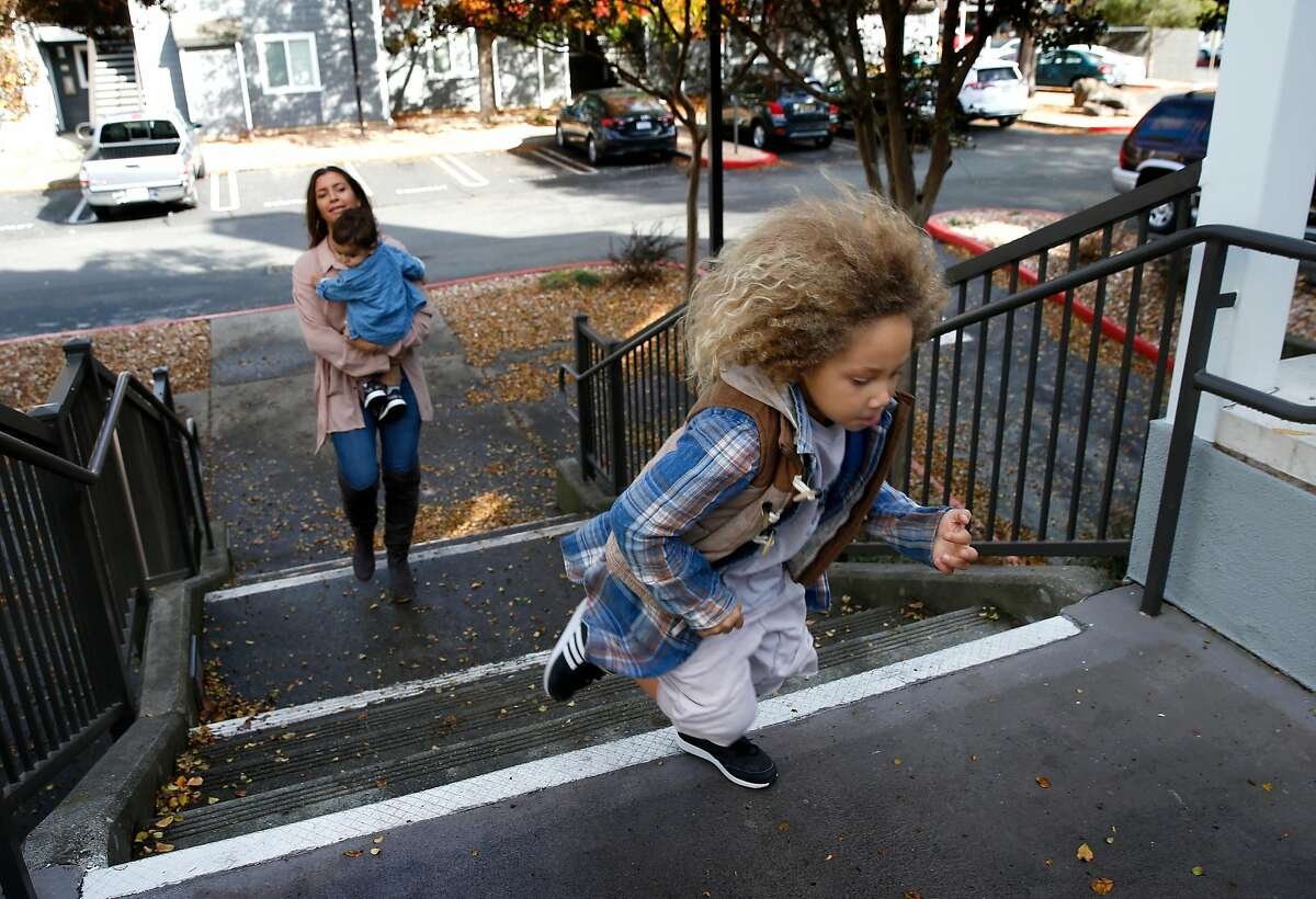 Five-year-old Kin races up the steps to his home ahead of his mother Kelli Peterson and younger brother Che, 1 after returning from a skatepark in San Rafael, Calif. on Saturday, Dec. 1, 2018.