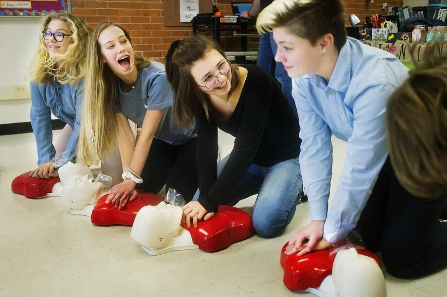 From left, Midland High students Emmy MacKenzie, 15, Olivia Post, 14, Dakota Mathey, 16, and Maddie Scott, 14, practice doing chest compressions during a CPR/AED training session hosted by paramedics and an EMT with MidMichigan Health on Tuesday, Dec. 4, 2018 at the school. (Katy Kildee/kkildee@mdn.net) Photo: (Katy Kildee/kkildee@mdn.net)