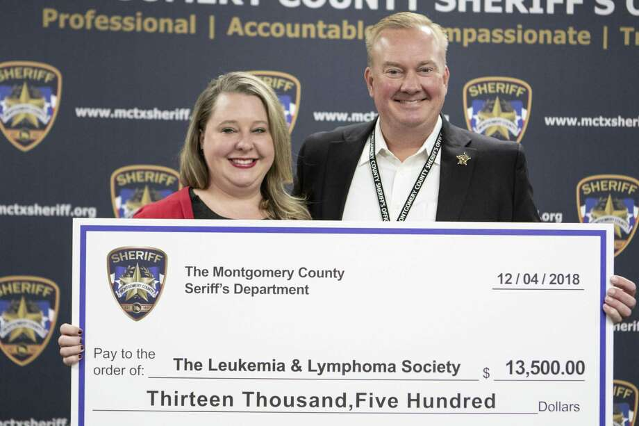 """Mindy Reynolds, Leukemia & Lymphoma Society campaign manager, accepts a $13,500 check from Montgomery County sheriff Rand Henderson. The money was raised through donations during """"No Shave November."""" Photo: Cody Bahn, Houston Chronicle / Staff Photographer / © 2018 Houston Chronicle"""